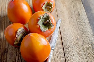 Ripe orange persimmons on an old woo