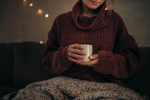 Woman having coffee in winter at hom