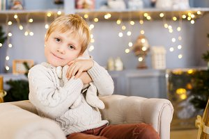 Boy sitting in chair on background of Christmas scenery