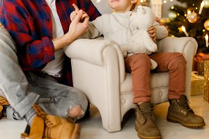 Festive image of happy son and dad on armchair