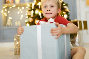 Photo of boy with gift box on background of Christmas decorations