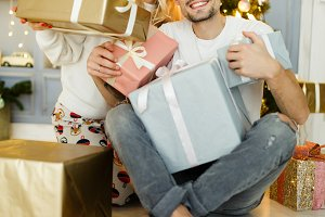Photo of man and woman in Santa hat with gift in box