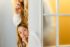 Photo of mother and daughter peeping out from behind door with Christmas wreath