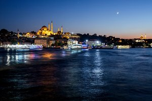 Istanbul cityscape with Suleymaniye mosque with tourist ships floating at Bosphorus at night