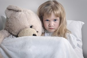 Sad little girl with plush bear in bed