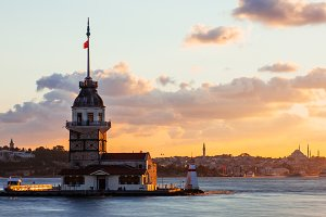 Maiden Tower or Kiz Kulesi with floating tourist boats on Bosphorus in Istanbul at sunset