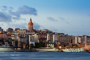 Istanbul cityscape with Galata Tower and floating tourist boats in Bosphorus