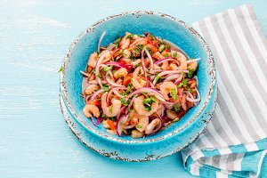 Ecuadorian shrimps ceviche sebiche with tomatoes in blue bowl, wooden blue background. Traditional ecuadorian colombian or mexican dish.