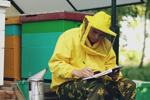 Young beekeeper man write in notepad checking harvest while sitting near beehives
