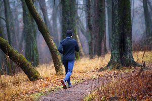 Trail running in autumn park. Young man jogging