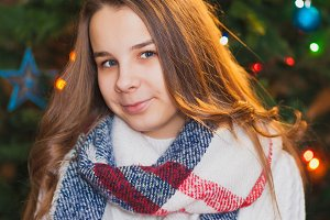 Beautiful teenager girl decorating the Christmas tree. Close-up portrait