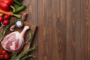 Raw goose leg and fresh vegetables
