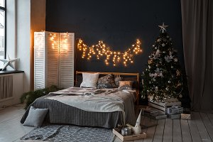 A spacious bedroom in a loft style with a decorated Christmas tree and a garland.
