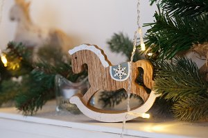 Rustic Christmas wooden horse toy on wooden surface, selected focus