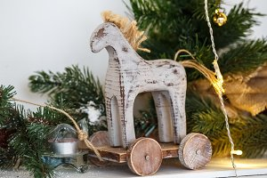 Rustic Christmas wooden horse toy on wooden surface, selected focus.