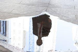 Businessman walking towards puddle