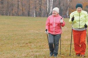 Happy elderly women in autumn park have nordic walking among autumn cold park