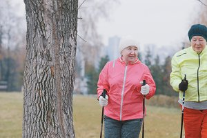 Sport for elderly women in autumn park - nordic walking among autumn park