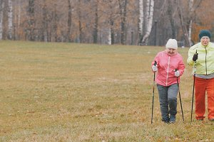 Training for elderly women in autumn park - nordic walking among autumn park