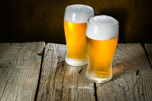 Beer in frosty mugs on rustic background