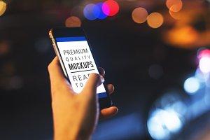 Hand holding mockup phone (PSD)