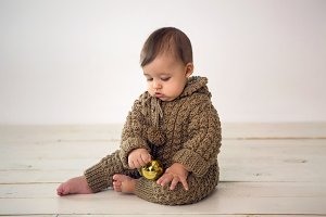 baby boy crawling on the floor in knitted