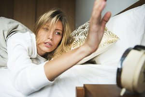 Woman turning an alarm off