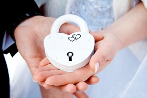 Hands and white lock. Wedding ceremony. The bride and groom loving couple bonded along their Union. The symbol and concept of eternity, love, beginning, new and old