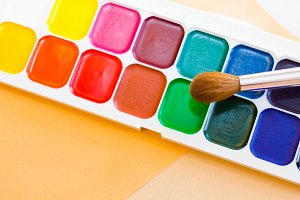 Palette of watercolor paints, brushes and paper for a water color on white background, close up. Selective focus