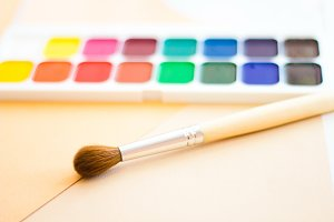 Palette of watercolor paints, brushes and paper for a water color on white background, closeup.  Selective focus