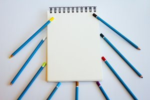 Notepad and pencils on the table on a white background. Space for labels and header.