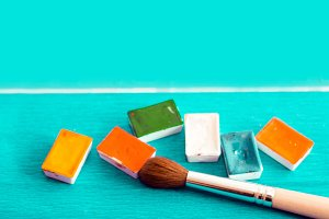Palette of watercolor paints and brush on a turquoise blue, blue background, closeup. Selective focus. Place for an inscription