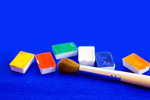 The palette of watercolor paints and brush on a blue background, closeup. Selective focus. Place for an inscription