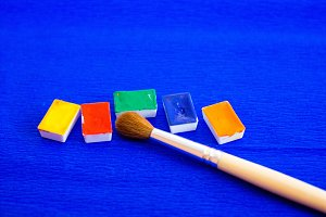 The palette of watercolor paints and brush on a blue background, closeup. Selective focus.Space for labels and header.