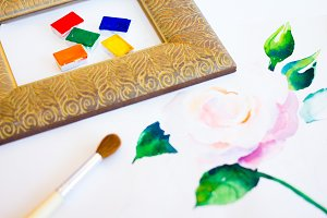 The palette of watercolor paints and brush and frame on a white background, closeup. Selective focus. Place for an inscription.