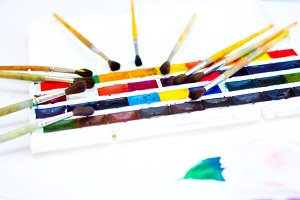 The palette of watercolor paints and lots of brushes on a white background, closeup.