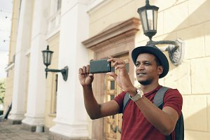 Mixed race happy tourist man taking photo on his smartphone camera standing near famous building in Europe