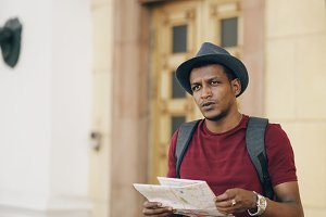 African american tourist man looking into paper city map exploring sightseeings during travelling in Europe