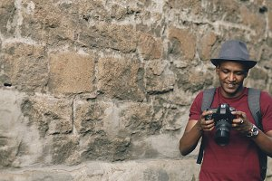 Mixed race happy tourist man taking photo on his dslr camera standing near famous building in Europe