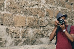 African american happy tourist taking photo on his dslr camera. Young man standing near famous building in Europe