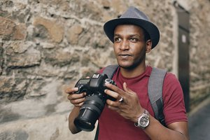 African happy tourist taking photo on his dslr camera. Young man travelling in Europe