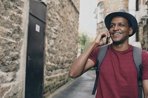 mixed race tourist walking and chatting phone. Young happy man travelling in Europe