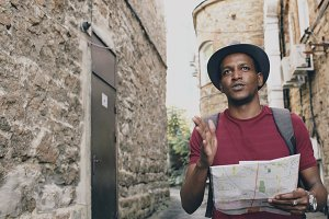 African american tourist man walking and watching paper city map to find directions to famous place