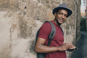 African american smiling tourist man using tablet online map to find right directions standing at street