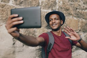 Happy african american tourist man having online video chat using tablet computer while travelling in Europe