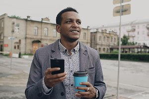 young happy businessman using smartphone and walking with cup of coffee outdoors