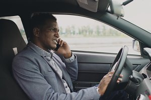 Angry mixed race businessman talking phone while sitting inside his car outdoors