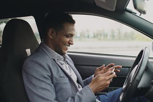 Happy african american businessman surfing social media on his tablet computer sitting inside his car