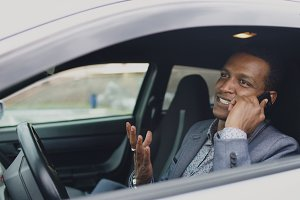 Happy mixed race businessman talking phone while sitting inside his car outdoors