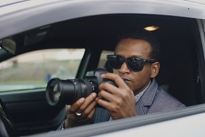 Private detective man sitting inside car and photographing with dslr camera